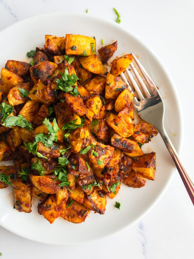 batata harra on a white plate with a fork