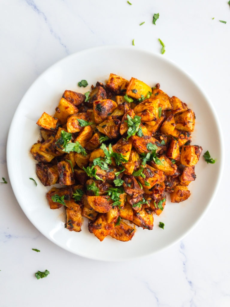 spicy potatoes (batata harra) on a white plate garnished with parsley