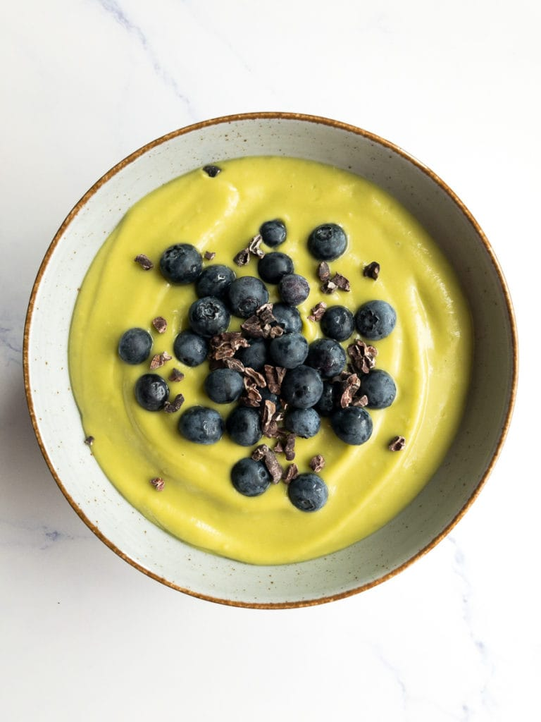 vanilla avocado pudding topped with blueberries in a bowl