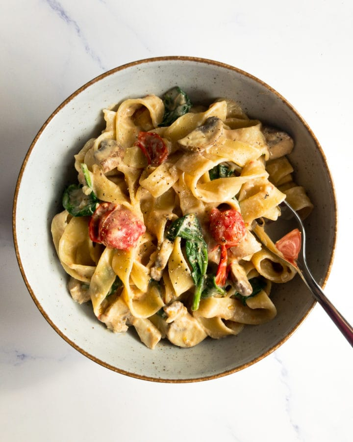 vegan fettuccine Alfredo with spinach, mushrooms and cherry tomatoes in a bowl with a fork