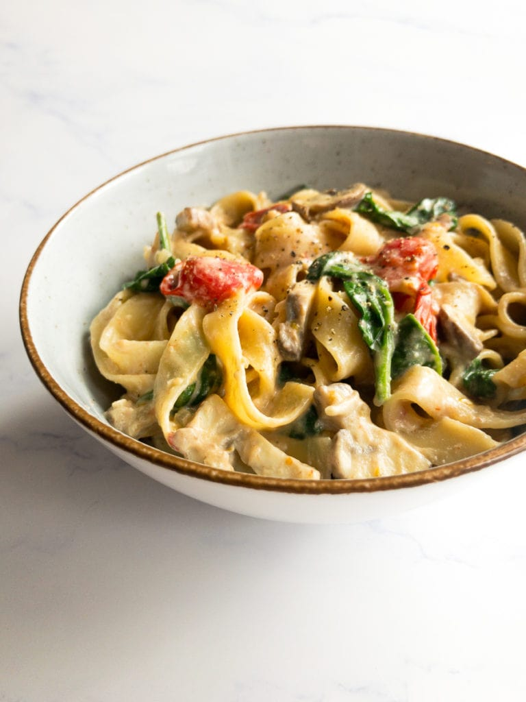 vegan fettuccine Alfredo with spinach, mushrooms and cherry tomatoes in a bowl