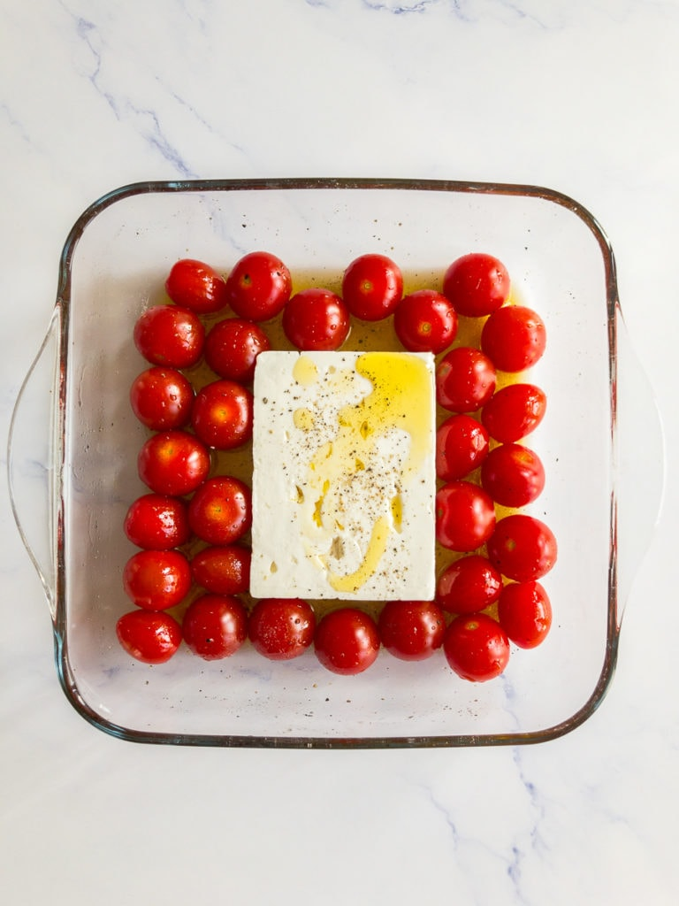 cherry tomatoes and a feta block in a baking dish, drizzled with olive oil and seasoned with salt and pepper