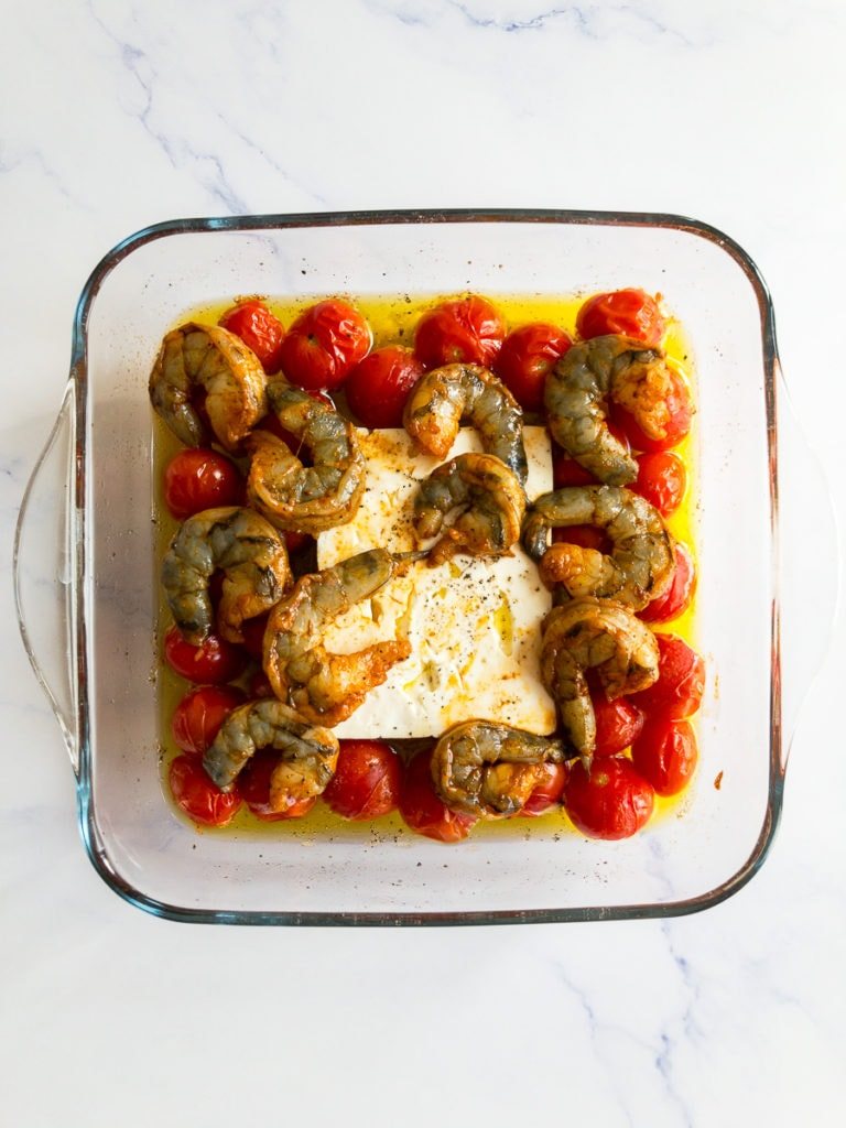 baked cherry tomatoes and a feta block in olive oil with added raw shrimp on top