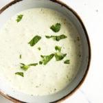 cilantro garlic sauce in a small bowl garnished with chopped cilantro