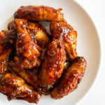 honey garlic chicken wings on a white plate