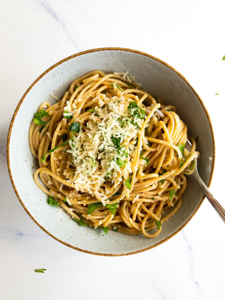 lemon garlic pasta in a bowl with a fork topped with grated parmesan and chopped parsley