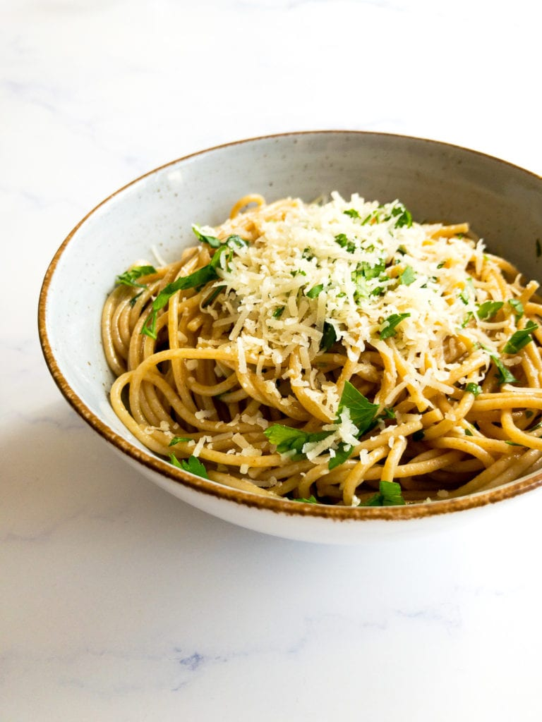 lemon garlic pasta in a bowl topped with grated parmesan and chopped parsley