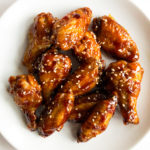 teriyaki chicken wings garnished with sesame seeds on a white plate