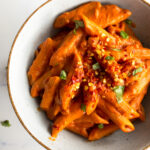 vegan penne alla vodka in a bowl topped with fresh basil leaves and red chili flakes