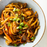 chicken yaki udon garnished with green onion and sesame seeds in a bowl