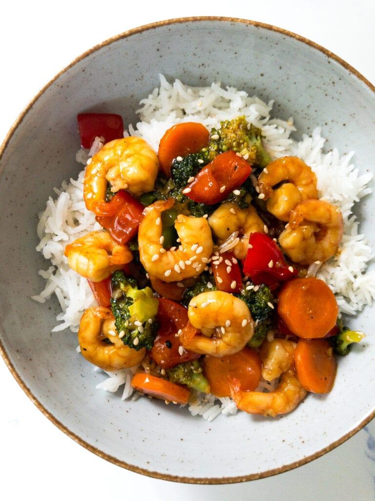 teriyaki shrimp stir fry served over white rice in a bowl