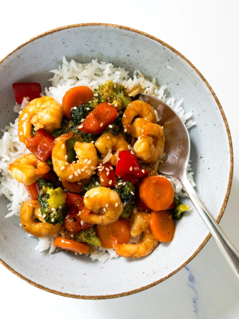 teriyaki shrimp stir fry served over white rice in a bowl and a spoon
