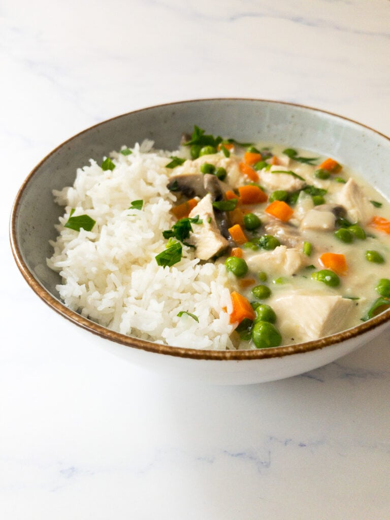 chicken fricassee in a bowl with white rice garnished with parsley