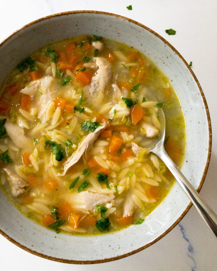 lemon chicken orzo soup garnished with parsley in a bowl with a spoon