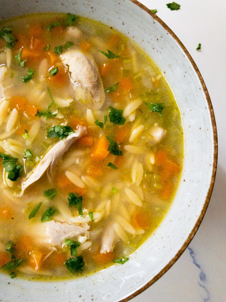 lemon chicken orzo soup garnished with parsley in a bowl